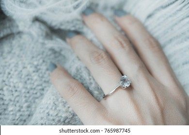 Close up of an elegant engagement diamond ring on woman finger with dark gray sweater winter clothe. love and wedding concept.