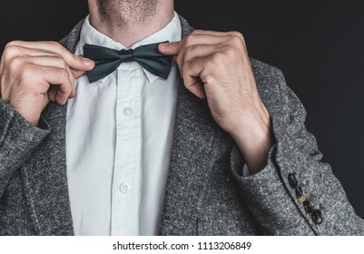 Close up of an elegant man in white shirt and grey vintage jacket tightening up a dark emerald colored bow tie on a black background. Getting ready for work, wedding or an event.