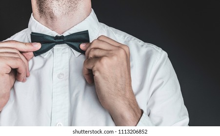 Close up of an elegant man in white shirt tightening up a dark emerald colored bow tie on a black background. Getting ready for work, wedding or an event.