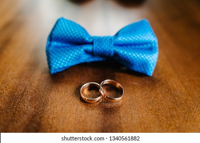Close Up of elegant stylish blue male bow tie and two golden rings isolated on a brown background. Preparation for wedding day concept.