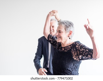 Close up of elegantly dressed older man and woman dancing exuberantly against neutral background (selective focus)