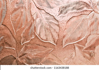 A close up of embossed door or window glass with a leaf pattern tinted peach pink