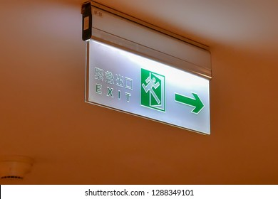 Close up of emergency exit sign write on Chinese and English word on ceiling inside shopping mall