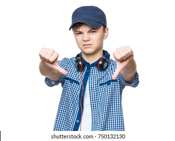 Close up emotional portrait of caucasian unhappy teen boy giving thumbs down hand gesture. Angry child looking with disapproval facial expression, isolated on white background. Negative human face