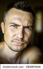 Close up emotional portrait of a caucasian unshaved man with blue eyes.