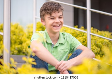 Close up emotional portrait of handsome caucasian smiling teen boy sitting on the stairs. Funny cute teenager in summer park looking away.