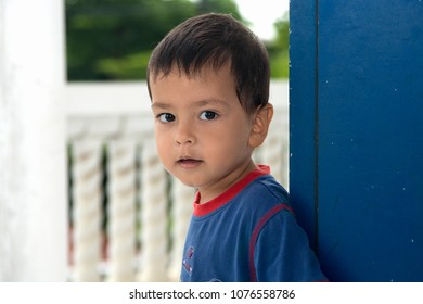 Close up emotional portrait of the little boy standing on a balcony at a blue door