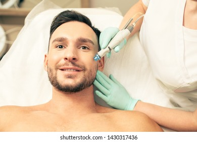 Close up of the emotional young man looking impressed and smiling while undergoing the skin nourishing procedure with a help of a modern tool