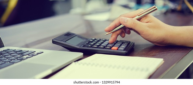 close up employee accountant man hand press on calculator for make financial report or company's profit monthly at desk , bookkeeper job concept