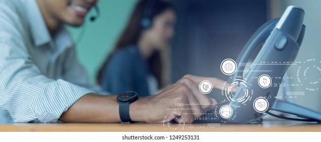 close up employee call center man hand point to press button number on telephone office desk with virtual communication technology concept