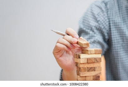 close up employee man hand holding wooden block for playing jenga game while working on laptop