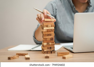 close up employee man hand holding wooden block for playing jenga game while working on laptop ,