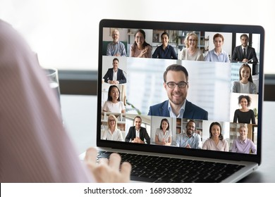 Close up of employee talk on video call on laptop with diverse colleagues, worker speak on web conference with multiracial coworkers, have online briefing with team, use Webcam on computer