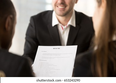 Close up of employers or recruiters holding reviewing cv of happy applicant smiling at background during interview, employment and recruitment concept, good resume template writing tips, apply for job