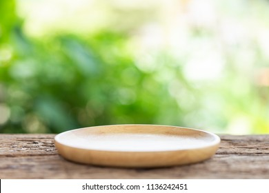 Close up empty dish on wooden table with green blur light background. For photo montage