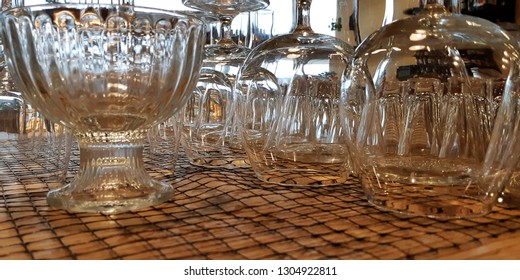 Close up empty glasses on the showcase in restaurant, prepare for dinning room.Pile of clean glasses.dry, transparent glasses stand in a row upside down