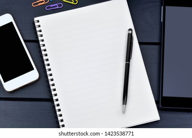 Close up of empty notebook with pen, phone and digital tablet on desk