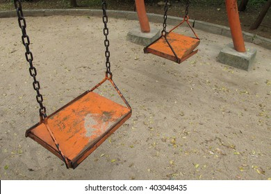 Close up of empty old wooden swing seats with faded paint and rusty chain on dry land.