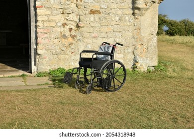 close up of empty wheelchair outside stone building on grass in summertime.  Disabled occupant inside dwelling leaving chair unoccupied