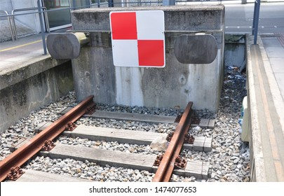 Close up of an end of train tracks, with concrete wall and metal bumpers, in a train station