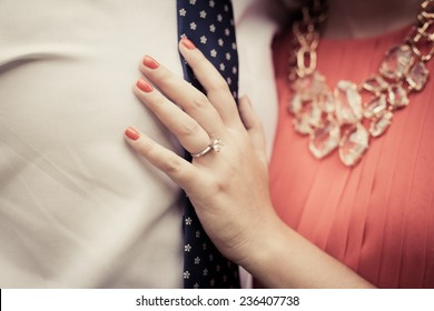 Close up of engaged couple showing diamond ring