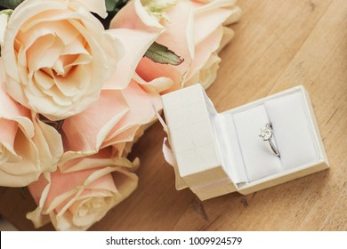Close up of engagement ring in gift box with rose flowers on wooden table. Marriage proposal concept by means of flower bouquet and gift. Wedding proposal for beloved woman