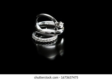 close up of engagement and wedding rings isolated on a black background