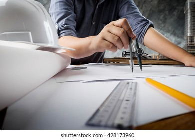 Close up of engineer hand sketching a construction project with Pencil, compass. Business meeting concept.