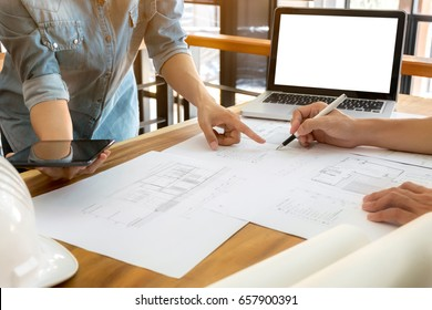 Close up of engineer hands discussing a building construction project with blank screen laptop at workplace