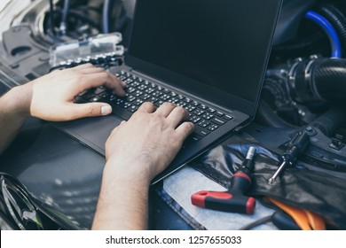 Close up engineer  mechanic using electrnoic diagnostic equipment to tune a car