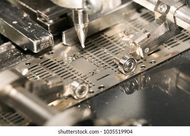 Close up epoxy stamping on lead frame in die attach machine in Semiconductor Manufacturing