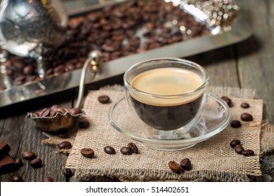 Close up espresso glass cup with coffee bean, chocolate and creamer on old wooden table