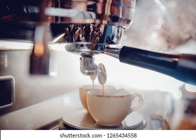 Close up of espresso pouring from coffee machine in two white cup. Professional cappuccino brewing. Background is blurred