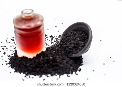 Close up of essential oil of kalonji or roman coriander or fennel flower seeds in a bowl isolated on white.