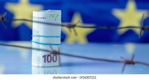 Close up EU money wrapped in barbed wire against flag of European Union as symbol of economic warfare, sanctions and embargo busting. Horizontal image.