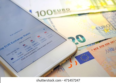 close up Euro banknotes background and exchange rates screen on mobile phone with selective focus . Currency exchange concept
