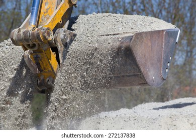 Close up of excavator bucket scooping gravel from pile for road construction