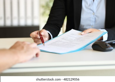 Close up of an executive hands holding a pen and indicating where to sign a contract at office
