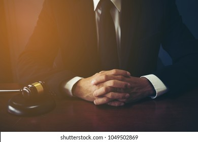 Close Up Executive Lawyer or Judge Hand Striking the Gavel on Sounding Block in LAW OFFICE , Justice and LAW concept background,