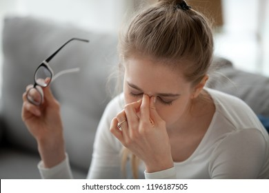 Close up exhausted young woman taking off eyeglasses massaging nose bridge feels eyes fatigue strain tension. After long computer use or reading a book girl suffering has eyesight problem discomfort