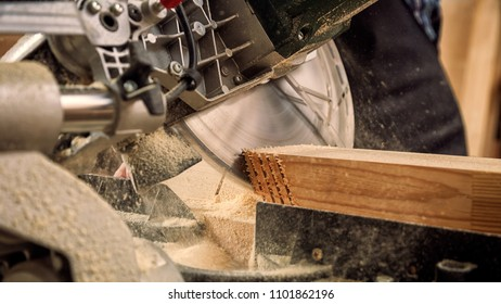 Close up of experienced carpenter in work clothes and small buiness owner working in woodwork workshop, using a circular saw to cut through a wooden plank, on the table is a hammer and many tools