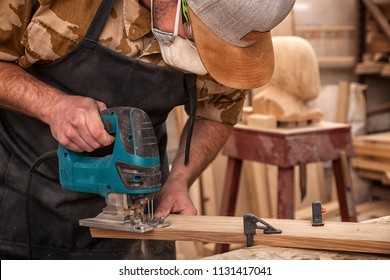 Close up of experienced carpenter in work clothes and small buiness owner  carpenter saw and processes the edges of a wooden bar with a jig saw  in a light workshop