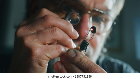 Close up of experienced goldsmith controlling a quality of rubin stone, selected for making jewels in workshop.Concept of jewelry,luxury,goldsmith, diamonds, brilliance.
