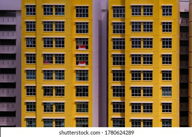 Close up of exterior of typical public housing (HDB flats) in bright, bold yellow, in Singapore on sunny day. Modern urban architecture concept. Abstract graphic; background.