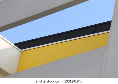 Close up exterior view from below of the top of a modern painted building. Geometric forms colored in white, gray, black and yellow. Opening with the blue sky in background. Many polygonal shapes.