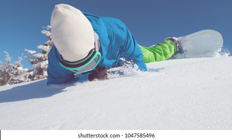 CLOSE UP Extreme male snowboarder riding off piste crashes head first into untouched powder snow. Pro freeride snowboarder on adrenaline filled ride down sunny mountain falls into freshly fallen snow