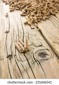 close up of extruded wood pellets on old cracked knotted wooden board with wood pellets out of focus behind