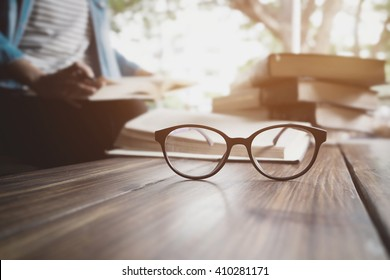 Close up of eye glasses on wood desk and text book in library. Education concept.