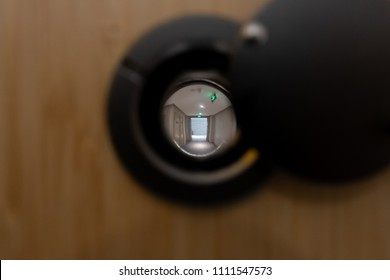 Close up eye hole on wood door looking to outside the room.