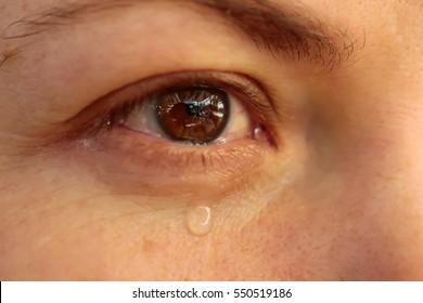 Close up of eye with tears. Tear drop on woman's eye. Sad girl cry